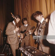 Wearing their stage suits, Paul McCartney, John Lennon (1940-1980) and George Harrison (1943-2001) of English pop group The Beatles tune their guitars at a sound check on stage at a venue during their autumn tour of the United Kingdom in 1963. (Photo by Popperfoto/Getty Images)