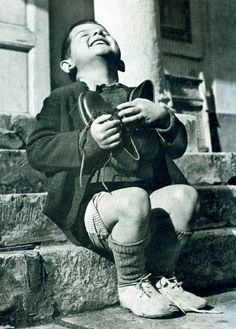 """""""New Shoes"""" by Gerald Waller, Austria 1946    Six year-old Werfel, living in an orphanage in Austria, hugs a new pair of shoes given to him by the American Red Cross."""