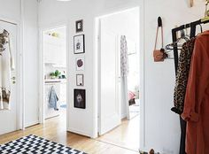 Discover inspiration for decorating your hallway wall located between two doors. Browse photos for decorating ideas for narrow walls throughout your home—from stools to large and small artwork, and much more.