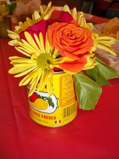 Centerpieces - flowers in Mexican tomato sauce cans.  Possibly a cute decor for us!