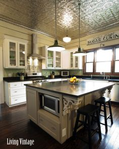 a vintage kitchen renovation - check out the tin ceiling, corbels, old signs, pantry screen door, and unique backsplashes!