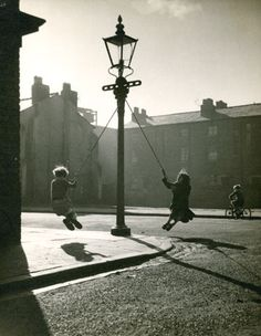 children swinging from ropes on a lamp post