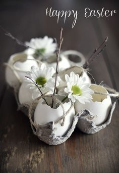 Different idea for an Easter centerpiece. Cute and Spring-y eggshell 'vases' in a carton, with daisy pompoms and twigs tucked in.