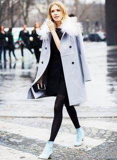 Elena Perminova wears a black dress, light gray coat, tights, and blue ankle boots