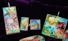 Alcohol ink painted by blowing through a straw on white Friendly Plastic inserted into a blank pendant tray.