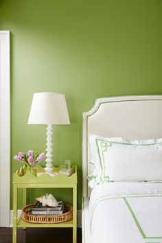 Meg Braff Designs - A white headboard lined with green piping accents a bed dressed in white and green Greek key bedding with matching shams complementing a Oomph Online Hobe Sound Side Table with Shelf lit by a Aerin Lilian Table Lamp placed in front of a green wall.