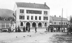 """Telemark fylke Notodden Notoddens Apothek"""" med torghandel i framgrunnen. Vi ser at Doktor E. Strømme har kontor i 2. etasje i apotekgården, og mellom apoteket og Notodden Teater lå """"Theatercafeen"""". Bildet må være tatt etter 1914 Street View"""