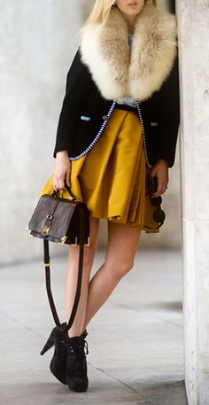 Fur collared coat and great pop of color from her mustard skirt