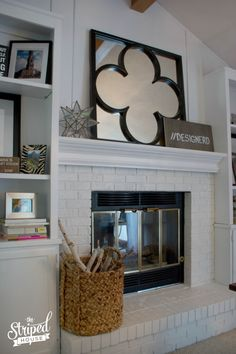 Transforming outdated stained wood bookcases and a dark brick fireplace to bright, white, modern and current space.