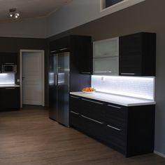 Hirsitalon kalustuksesta haluttiin moderni vaikka talon rakennusmateriaali onkin perinteinen. Talon sydän on iso nykyaikainen tupa, missä keittiö yhdistyy oleskelutilaan.  Tumma keittiö sopi hyvin tilaan koska väritys oli muuten vaalea ja isot ikkunat antavat valoa. Keittiön ovimallina on kaunis eläväpintainen kalvo-ovi vaakakuviolla. Korkeassa tilassa matala yläkaapisto on keveä. Iso, Kitchen Island, Home Decor, Island Kitchen, Decoration Home, Room Decor, Home Interior Design, Home Decoration, Interior Design