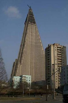 The Ryugyong Hotel resides in N. Korea. Work began in 1987 and was abandoned in 1992. At 105 stories, with 7 revolving restaurants, it would have been the tallest hotel in the world. However, word has it that is suffers from crumbling concrete, problems with the elevator shaft, and funds to complete it.