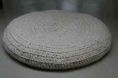 Large flat crocheted pouf (100%) off-white-colored wool with leather bottom.