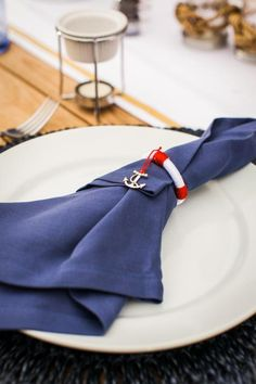 Lifesaver rings with anchor charms slipped over blue cloth napkins complete the nautical themed table decorations.Videos: Watch creative how-to's on nautical-inspired entertaining ideas >>