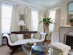 This cream and white living room is furnished with traditional decor and has beautiful oversized curtains.