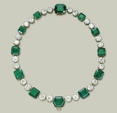 A MAGNIFICENT EMERALD AND DIAMOND NECKLACE, BY CARTIER  Set with twelve octagonal and hexagonal-cut emeralds, weighing a total of approximately 108.74 carats, with twin old European-cut diamond spacers, weighing a total of approximately 59.36 carats, mounted in gold collets with heart-shaped galleries, 1937, modified at a later date to create the pair of earrings en suite (lot 214), 45.0 cm By Cartier, no. E 6992 A