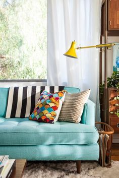Love the turquoise sofa, the stripe fabric and the colourful pillow. The yellow lamp compliments the sofa. Natural colour rug and wood furniture balance the bright colours.  Bri Emery's New Living Room, designed by Emily Henderson, shot by Laure Joliet