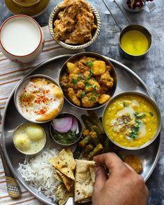 @funfoodandfrolic • Punjabi thali.  :: daal tadka, wadiya Aloo, Dahi baalla, Bhindi Masala, Dum Murgh, green chutney, methi mathri and ras malai