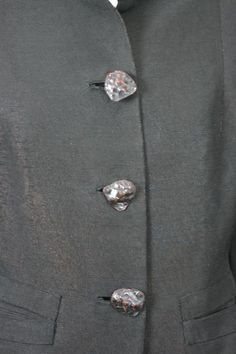 """Chic faille Haute Couture evening jacket by Schiaparelli from the early 1940's. Innovative and extraordinary changeant black faille(experimental metal fabric) which shifts from iridescent red to blue with amazing """"turtleback"""" enamelled button closures. Sharply cut with strong shouldered modified leg of mutton sleeves, pinched waist and applied slash pockets. Sober and severe chic that Schiaparelli espoused just before the onset of WWII. Schiaparelli,London, 1940's."""