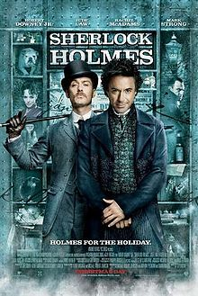 """Robert Downey, Jr. and Jude Law, in-character. The background is a window display, featuring shelves containing miscellaneous objects relating to the story. The poster reads """"Sherlock Holmes"""" across the top, with the tagline """"Holmes for the holiday"""" centered at the bottom. The poster is predominately turquoise coloured."""