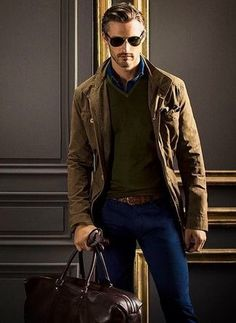 Men's Dark Brown Sunglasses, Navy Longsleeve Shirt, Olive V-neck Sweater, Brown Military Jacket, Brown Woven Leather Belt, Dark Brown Leather Gloves, Blue Skinny Jeans, and Dark Brown Leather Holdall