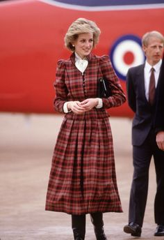 Diana added a white-bibbed blouse and black boots to her long-sleeved, calf-length dress.