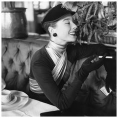Woman modeling black velvet visor with rhinestone pin and satin scarf, both by Dior 1952 Photo Henry Clarke