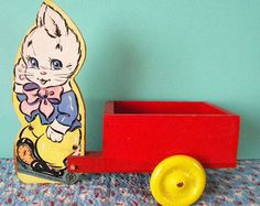 This is definitely one of my favorite Fisher Price toys from days gone by. This bunny wagon is so bright and cheerful-the perfect display piece at Easter but can hold its own all year round. This is made of wood composite with the paper applied to the top. This cart is in nice condition-still so bright but does have a corner missing on one end of the cart. The initials KAW and 1965 are written in pencil on the bottom. Measures 7.5 x 7 and is 4.25 deep.  **Please convo me for an accurate…