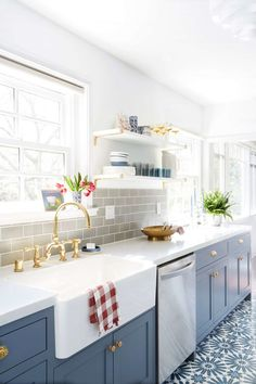 blue kitchen cupboards with gold faucet tap and open shelving with pattern tile floor
