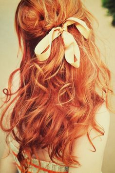 Cute red hair with soft curls and half ponytail with bow