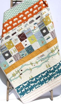 This modern quilt was created using Camp Sur by Jay Cyn Designs for Birch Organic Fabrics which is 100% GOTS certified organic cotton. The colors blend so well yellow, navy blue, sky blue, teal, deep purple, orange and ivory. It measures approximately 39 by 46 perfect for a baby as