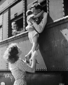 Wife of a departing soldier lifts her son for farewell embrace. Oklahoma, 1945. by adele