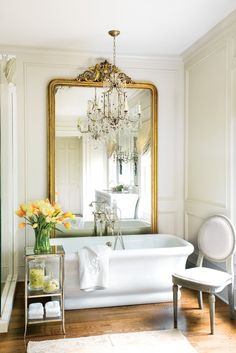 Chic Parisian style bathroom with luxurious soaking tub in front of large decorative carved gilt framed mirror. A simple table with a vase a beautiful orange flowers and classic white chair are perfect next to the pretty tub. The striking gold and crystal chandelier add a touch of glamour and romance to the space.