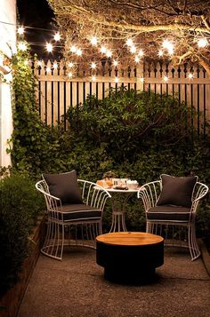 Small Patio Ideas: Outdoor string lights cast a lovely glow on a small patio at night.