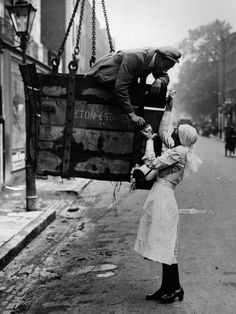 a worker being lowered in a crane to buy a rose from a charity worker on alexandra rose day in baker street, london, 1916