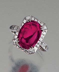RUBY AND DIAMOND RING.  The cabochon ruby weighing 5.70 carats, set within a frame of square-cut diamonds, mounted in platinum,