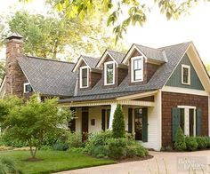 This charming cottage-style home features a pleasing mix of earthy colors and textures. Dark-stained shakes blend nicely with the natural stone chimney while small doses of white provide contrast. Cutout patterned shutters painted dark green add color and detail./