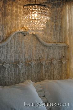 A vintage vent hood & bedspreads are now a canopy for a bed & a chandelier is hung under the canopy. The bedspreads hide the wiring for the lighting. This is very creative!
