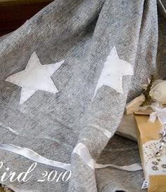 An easy, quick and cheap Christmas tree skirt made from a moving blanket and some felt stars. See more details at http://www.songbirdblog.com