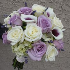 wedding bouquet with purple flowers. Cala lillies and roses, the teardrop shapes are a nice contrast in with the round roses