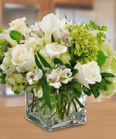 Pure and white, this contemporary cube or cylinder style arrangement will make a lovely gift or centerpiece.
