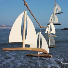 A beautiful garland featuring six dainty little driftwood sailboats bobbing about a natural twine rope. The yachts have sails made from tin and the rope has loops at either end of easy hanging.