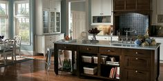 Brown cabinetry that is paired perfectly with a light blue counter-top. The wall unit in the back is quite unique.