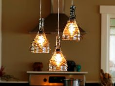 Wine Bottle Pendant Lights You can make so many things with a bottle cutter. For instance, these kitchen pendants were crafted from three old wine bottles. Cut just below the neck, wrapped in decorative wire then fitted with electrical fixtures. Empty Wine Bottles, Recycled Glass Bottles, Wine Bottle Art, Lighted Wine Bottles, Bottle Lights, Wine Bottle Crafts, Glass Lights, Wine Glass, Glitter Bottles