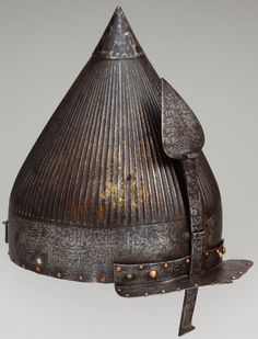 """Ottoman chichak, a type of helmet (migfer) originally worn in the 15th-16th century by cavalry (sipahi) of the Ottoman Empire, steel, engraved and gilt Dimensions: Height, 10 1/2 in. (26.67 cm). Bequest of George C. Stone, 1935, inscribed around the rim, a verse from the Koran known as the Victory Sura (48:1–4), includes the phrase: """"Verily, we have granted thee a manfiest victory."""" Verses from this sura were used frequently on Ottoman armor and weapons in the sixteenth century."""