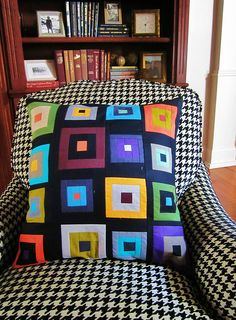 A colorful Log-Cabin style pillow (by Mary Clyde) on a black & white chair