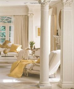 Grecian columns grace this formal living room decorated in soft ivory and gold. I love the cornices and the beautiful transom above the French doors....V