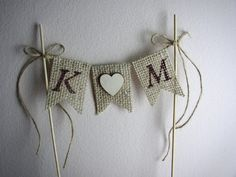 Rustic Wedding Burlap Cake Topper Banner with one wooden heart between letters and twine bow on each bamboo stick. Hand painted in brown lettering.