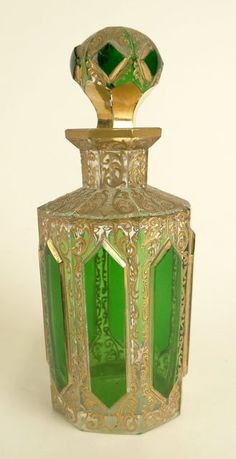 19/20th Century Moser Cut and Gilt Emerald Crystal - Scent Bottle with Stopper. Unsigned. Minor Chips to Stopper, Flake to Base and Rubbing to Gilt Decoration Otherwise Good Condition. Measures 5-1/4 Inches Tall and 2-1/4 Inches Wide.