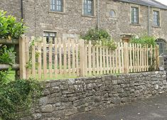 Cleft chestnut picket fence with sawn oak posts viewed from the road