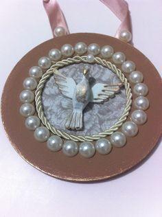 Medalhão Divino Espírito Santo para porta, feito em disco de MDF, com pintura em tinta na cor capuccino, acabamento em pátina dourada, aplicação de pérolas, tecido com estampa Toile de Jouy, com cordão São Francisco e Divino.